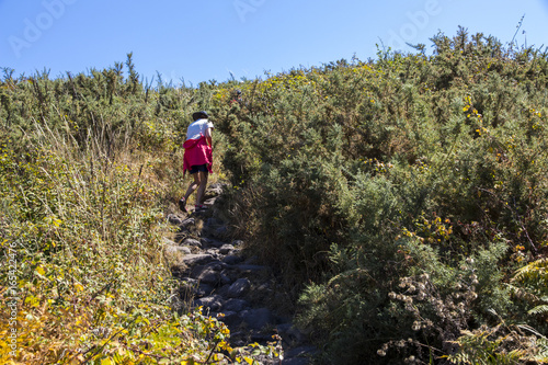 Poster Woman walks the trail leading to the top of Monte do Facho in Cangas, Galicia, S