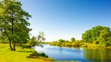 Sommerliche Landschaft mit Wiesen und Fluss - 165427849