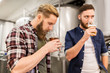 men drinking and testing craft beer at brewery - 165446412