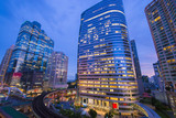 Bangkok business intersection at dusk. Location is Sathorn-Naratiwas road with office buildings and hotels around.