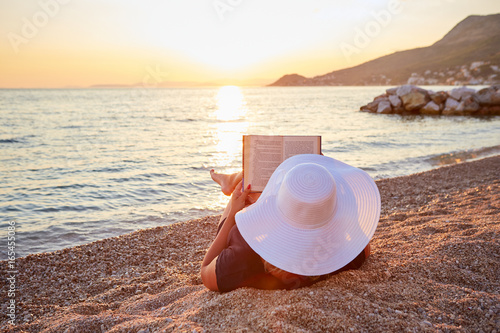 Woman reading a book on the beach at sunset