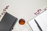 Flat composition cup with tea, books, pads, pen, purple dry flowers