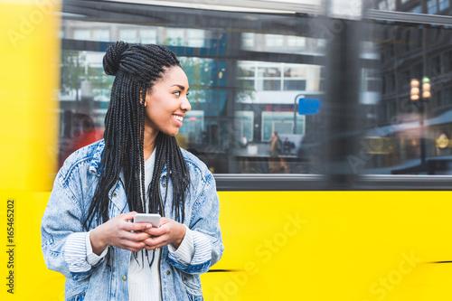 Deurstickers Berlijn Black girl typing on smartphone in Berlin