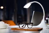 Office desk at night with eyeglasses, lamp and tablet.