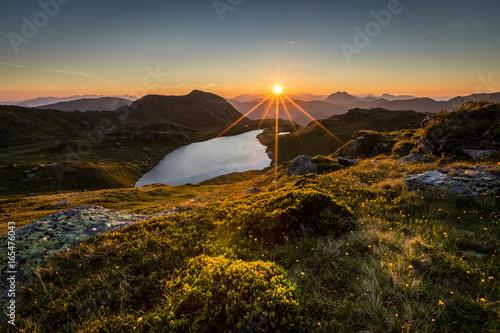 Sonnenaufgang über See am Berg mit Blumen und Steine im Vordergrund