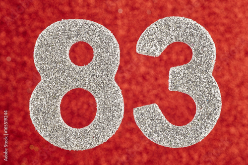 Poster Number eighty-three silver color over a red background