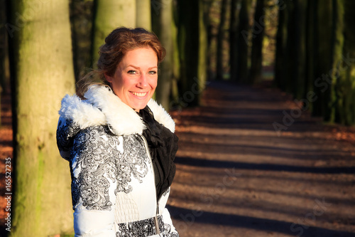 Winter portrait of a very beautiful young woman in the forest in the afternoon sun in the Netherlands