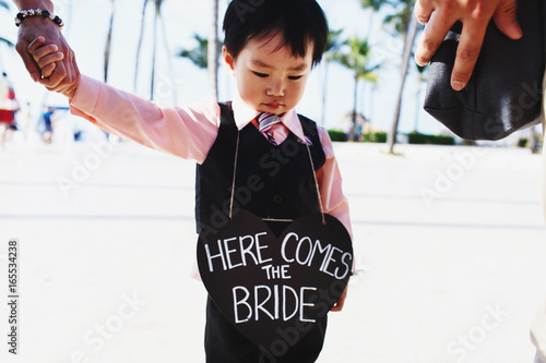 Little child holds black heart with lettering 'Here comes the bride' Poster