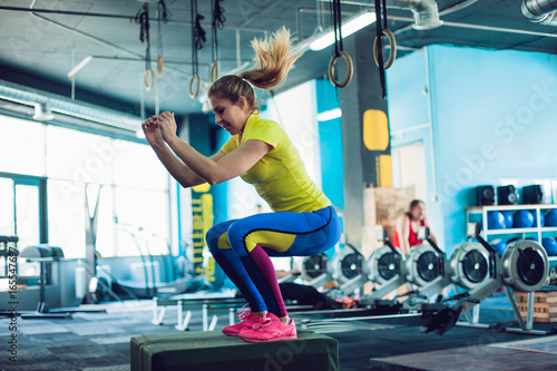 Fitness woman jumping on box training at the gym, girl in leggins and a t-shirt