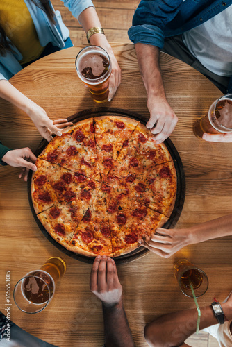 Top view group of young friends having pizza in cafe