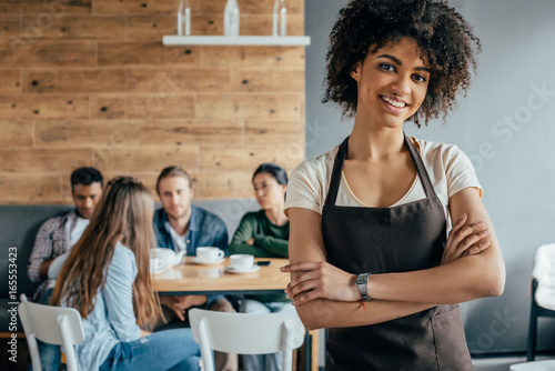 Smiling african american waitress standing with customers sitting behind in cafe