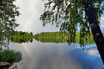 Landscape with rainbow on shore of lake