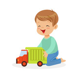 Cute happy little boy sitting on the floor playing with toy truck, colorful character vector Illustration