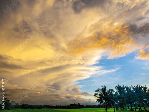 Staande foto Meloen A dramatic sunset sky looms over the rice fields and palm trees of east Thailand