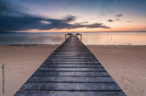 Seascape sunset with long expose effect with wooden jetty. Image contain soft focus due to long exposure.