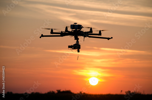 Professional drone flying at the sunset on red sky Poster