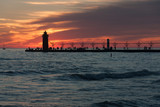 Dramatic photo of lighthouse and pier at sunset.