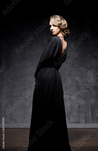 Young and gorgeous woman over dark dramatic background. Poster