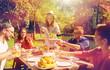 happy friends having dinner at summer garden party - 165589860