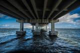 under large concrete bridge over ocean