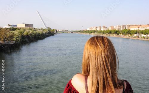 Young girl looking over the Guadalquivir river in Seville, Spain