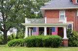 old brick home with hanging American flags on front porch with white columns - 165605857