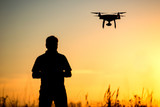Young man operating of flying drone the setting sun - 165606046