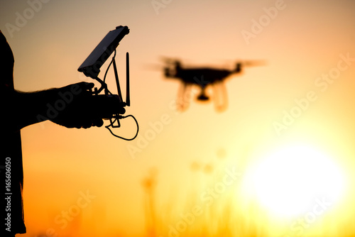 Young man operating of flying drone the setting sun Poster