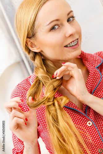 Woman doing braid on blonde hair © Voyagerix
