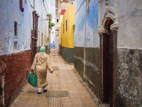 A Muslim Woman Walks Down A Colourful Street in Morocco
