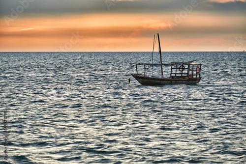 landestypische Dau schaukelt im Meer bei Sonnenuntergang, Sansibar, Tansania, Afrika