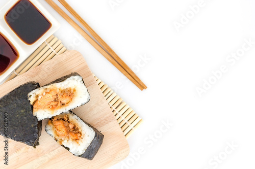 Japanese salmon rice wrapped in seaweed on wood plate isolated on white background with Copy space and text.