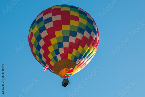 Mongolfiera multicolore vola nel cielo - 165652869