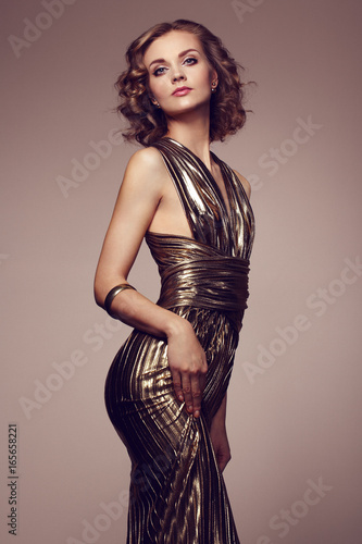 Fashion portrait of young beautiful woman in gold dress. Brunette glamour lady with perfect make up and hairstyle