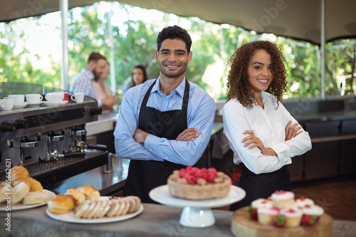 Portrait of smiling waiter and waitress standing with arms crossed at counter