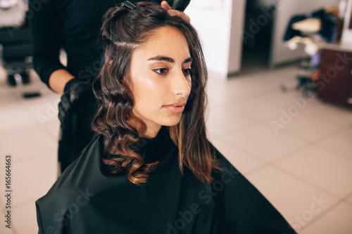 Stylist curling woman's hair in beauty salon
