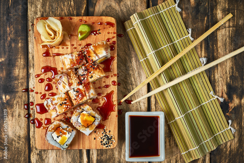 Sushi, rolls with eel on a wooden stand.