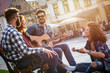 Group of people hangout at the city street.They sitting on bench ,singing and playing guitar.