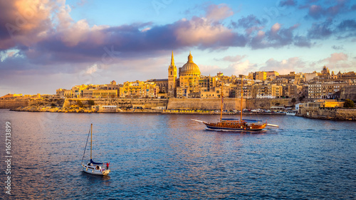 Valletta, Malta - Sail boats at the walls of Valletta with Saint Paul's Cathedral and beautiful sky and clouds in the morning