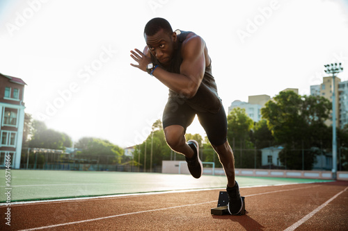 Young african runner running on racetrack Poster
