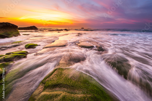 Colorful sunset with green moss at Kudat Sabah Malaysia. Image contain soft focus due to long exposure.