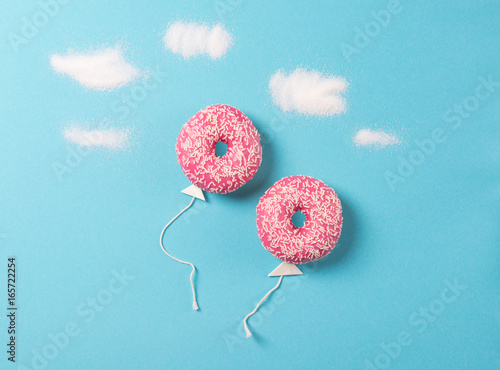 Pink donuts on blue background, creative food minimalism, donut in a shape of ba Poster