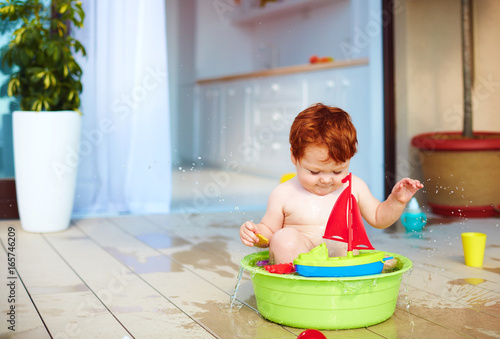 Fototapeta cute redhead toddler baby having fun with water on summer terrace
