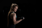Portrait of blonde female exercising with dumbbell