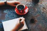woman hand writing notebook in cafe