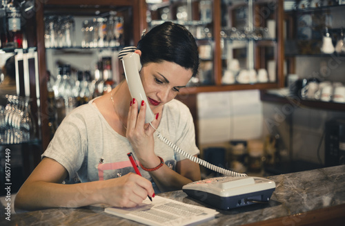 Young woman working at the pizzeria and writing order while talking on the phone