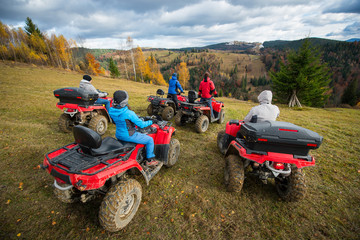 Rear view group of five person riding quad bikes on hill and enjoying beautiful autumn scenery of colorful trees in the forest and mountainous areas