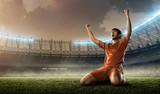 soccer player in red uniform celebrates a goal on a soccer stadium holding hands above his head and screaming - 165789025