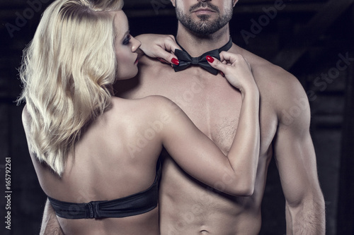 Sensual blonde woman straighten bow tie on naked sexy man Poster