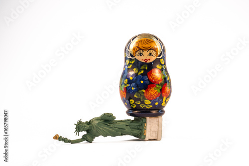 Russian babushka doll standing on top of the fallen Statue of Liberty Poster